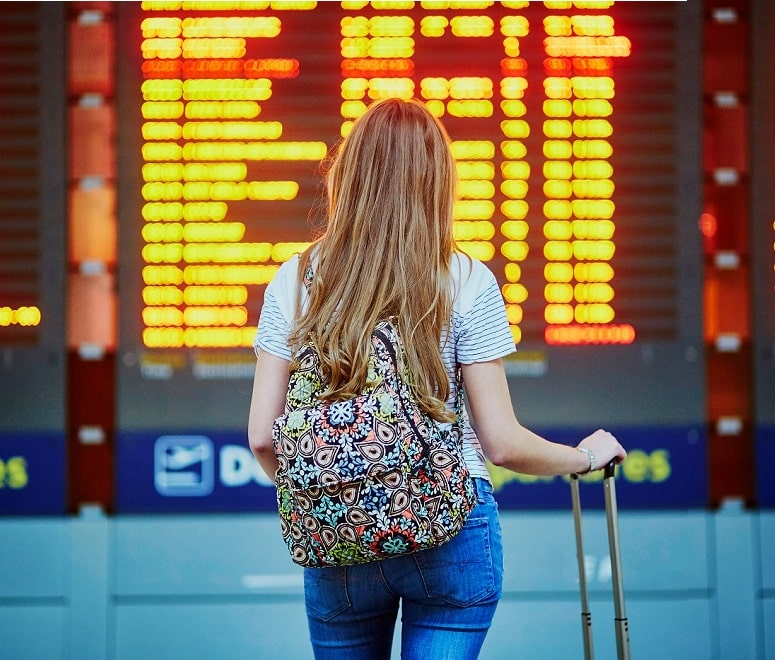 woman looking at airport board