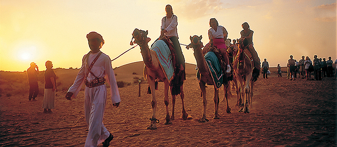 An image of people on camels in Dubai